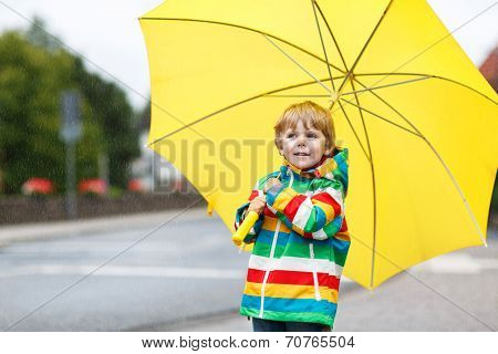 Adorable Toddler Boy With Yellow Umbrella And Colorful Jacket Outdoors At Rainy Day