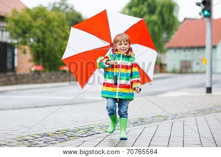 Beautiful Child With Yellow Umbrella And Colorful Jacket Outdoors At Rainy Day