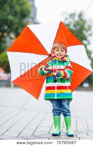 Cute Little Boy With Yellow Umbrella And Colorful Jacket Outdoors At Rainy Day