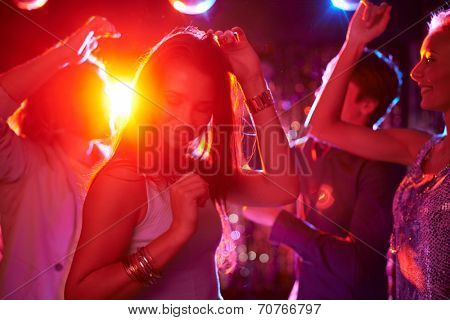 Pretty girls dancing in night club on background of guys