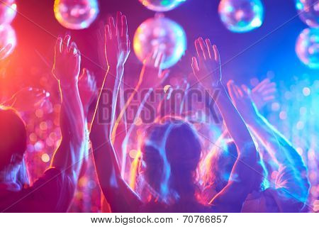Crowd of young people dancing in night club