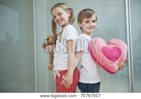 Boy and girl with heart shape cushion and teddy bear holding hands while standing back to back