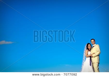 Wedding Couple Against Natural Blue Sky In The Evening Copy Space