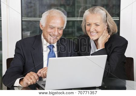 Happy senior business couple looking at laptop white sitting at table