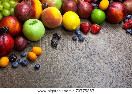 Border of mixed fruits with water drops on beautiful wooden texture - copy space