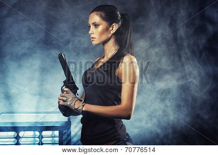 sexy woman standing on ruins and holding handgun