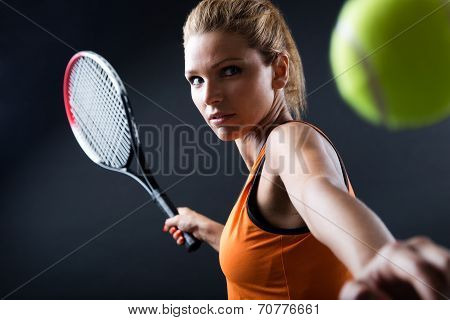 Beautiful woman playing tennis indoor.