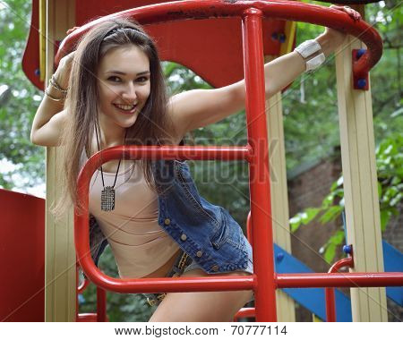 Happy teen girl has fun  on child hillock on playground. Outdoors. Image toned and noise added.