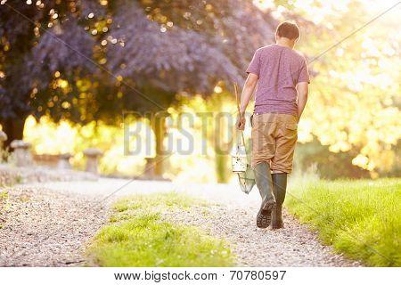 Boy Walking Along Path Carrying Fishing Net And Jar