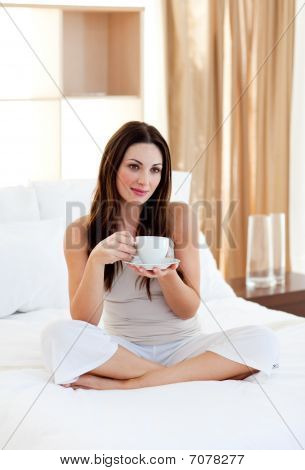 Attractive Woman Drinking Coffee Sitting On Bed