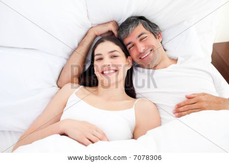 Smiling Couple Hugging Lying In Their Bed