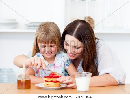 Merry Little Girl And Her Mother Having Breakfast