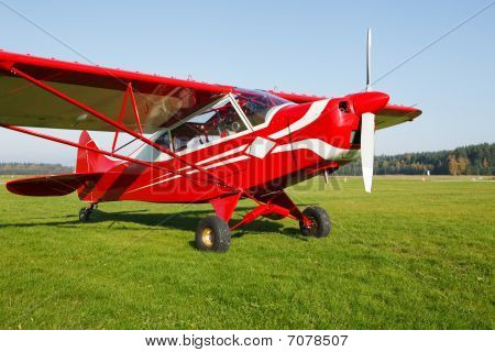 Small Airplane On Airfield Grass