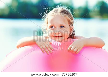 happy girl and swim ring at the beach. toned image