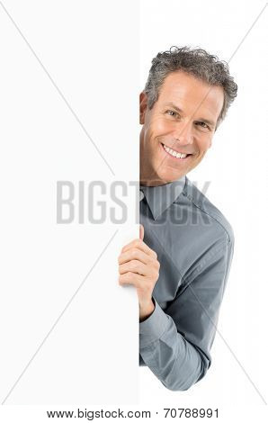 Portrait Of Mature Businessman Holding Blank Billboard Looking At Camera Isolated On White Background
