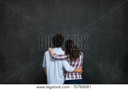 Young Couple Looking At Their Future Over Gray Background Ready For Your Product Or Text