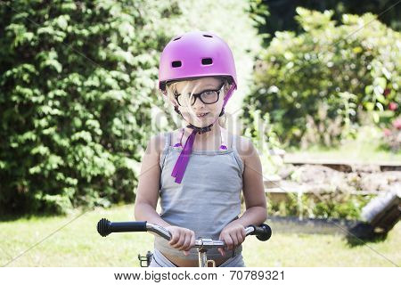 Child With Pink Bicycle Helmet And Black Glasses On Bike