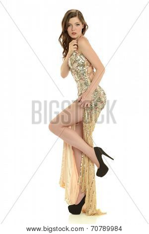 Young fashion model wearing a sparkling dress isolated on a white background