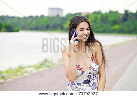 Happy beautiful girl calling by phone in a summer park