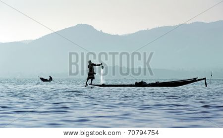 Traveling to Myanmar, outdoor photography of fisherman on traditional boat. Intha people from Shan state of Burma