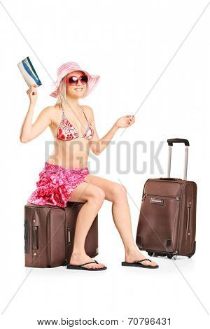 Woman holding a ticket seated on her baggage isolated on white background