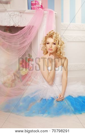 Cute woman looks like a doll in a sweet interior. Young pretty smiling girl