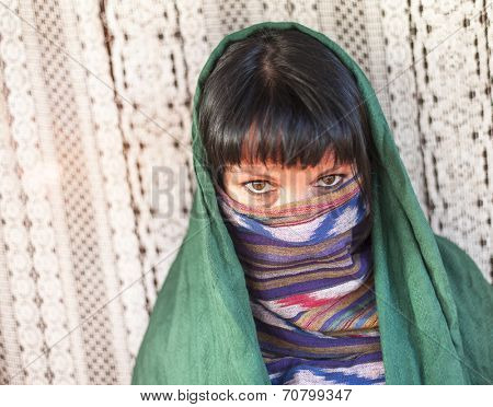 Young girl covers her face with a veil. Hijab.