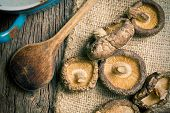 foto of edible mushrooms  - top view of dried shiitake mushrooms on table - JPG