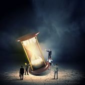 foto of hourglass figure  - Conceptual image of business people looking at sandglass - JPG