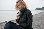 stock photo of poetry  - Woman writing her thoughts or poetry by the sea - JPG