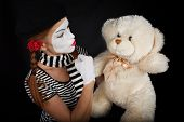 picture of clown rose  - Portrait of a mime comedian talking with teddy bear on black background - JPG