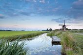 picture of windmills  - Dutch windmill by river at sunset Holland - JPG