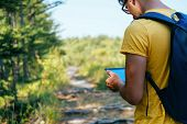 picture of gps  - Hiker young man searches GPS coordinates on tablet PC in the forest - JPG
