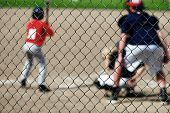 stock photo of umpire  - Baseball player batting with umpire behind fence - JPG