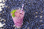 foto of mints  - Blueberry smoothie in a glass jar with a straw and sprig of mint with fresh berries - JPG