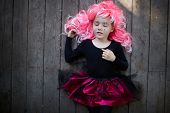 stock photo of antichrist  - Portrait of cute girl in pink wig having a nap - JPG