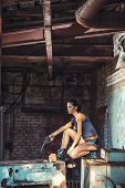 image of handgun  - sexy brutal woman sitting in factory ruins and holding handgun - JPG