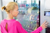 stock photo of coins  - Caucasian woman wearing pink top using a coin operated modern vending machine - JPG