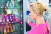 stock photo of women rights  - Caucasian woman wearing pink using a modern vending machine - JPG