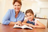 stock photo of granddaughter  - Grandmother Reading With Granddaughter At Home - JPG