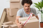 picture of fragile  - Portrait Of A Young Man Packing Cardboard Box With Fragile Sellotape - JPG