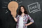 picture of lightbulb  - Happy Woman Holding Large Lightbulb Sign Over Gray Background - JPG