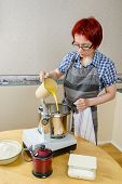 stock photo of food processor  - Woman adding mixture of milk and melted butter into food processor when baking - JPG