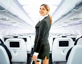 picture of cabin crew  - beautiful flight attendant on board of big plane - JPG