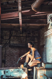 stock photo of raider  - sexy brutal woman sitting in factory ruins and holding handgun - JPG