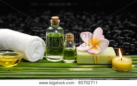 Still life with, frangipani and candle, soap ,salt in glass with row of plant stem