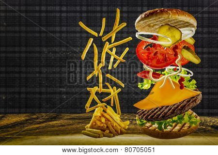 Delicious french fries and cheeseburger stacked high with a juicy beef patty, cheese, fresh lettuce, onion and tomato with flying ingredients and copyspace