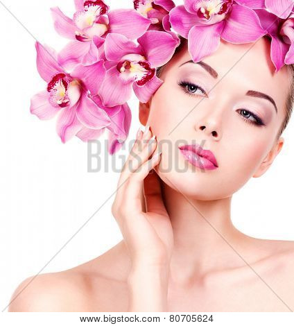 Closeup face of an young beautiful woman with a purple eye makeup and lips. Pretty adult girl with flower near the face.  - isolated on white background