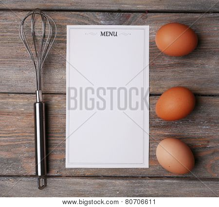 Menu sheet of paper with egg whisk and eggs on rustic wooden surface background