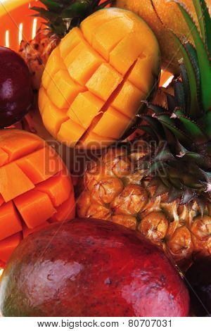 diet food - a lot of fresh raw tropical fruits include pineapple red plum and green mango in orange colander isolated over white background